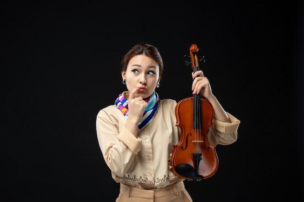 Вид спереди скрипачка держит свою скрипку, думая на темной стене, музыкальный концерт, инструмент, женщина, эмоция, играет, мелодия.