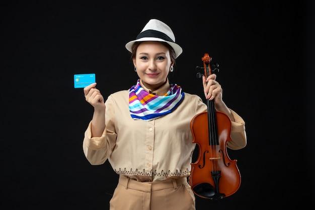 Vista frontale violinista femminile che tiene violino e carta di credito sulla parete scura melodia strumento musica emozione concerto spettacolo performance woman