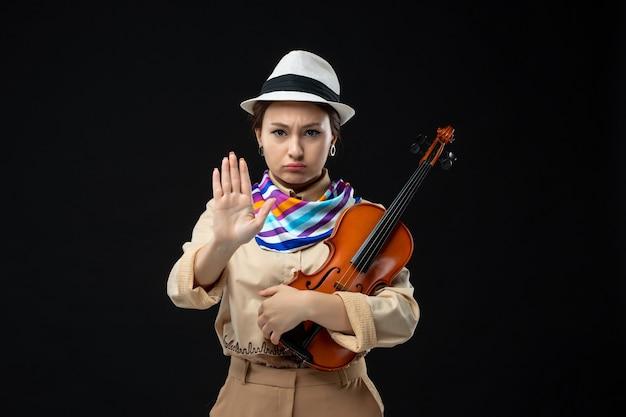 Вид спереди скрипачка в шляпе держит скрипку на темной стене мелодия инструмент музыка эмоция концерт играть производительность женщина