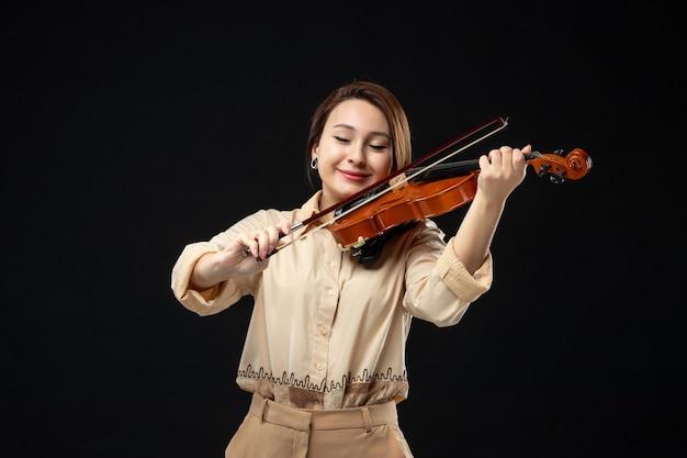 暗い壁の楽器でバイオリンを弾く正面図の女性バイオリニストはメロディー感情の女性を演奏します