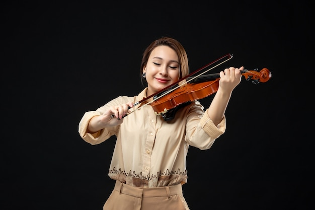 Violinista femminile vista frontale che suona il violino su uno strumento musicale da parete scuro suona donna emozione melodia