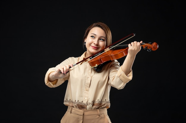 Vista frontale violinista femminile che suona il violino con il sorriso sul viso sullo strumento da concerto di musica da parete scura suona la melodia emozione donna