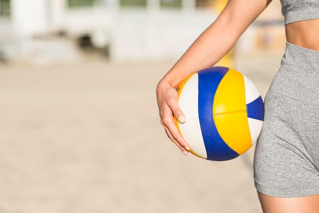 Front view of female volleyball player on the beach holding ball with copy space