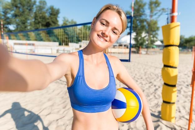 Vista frontale del giocatore di pallavolo femminile che prende selfie con la palla