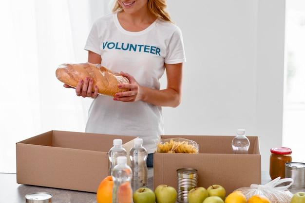 Vista frontale del volontario femminile che prepara le donazioni di cibo
