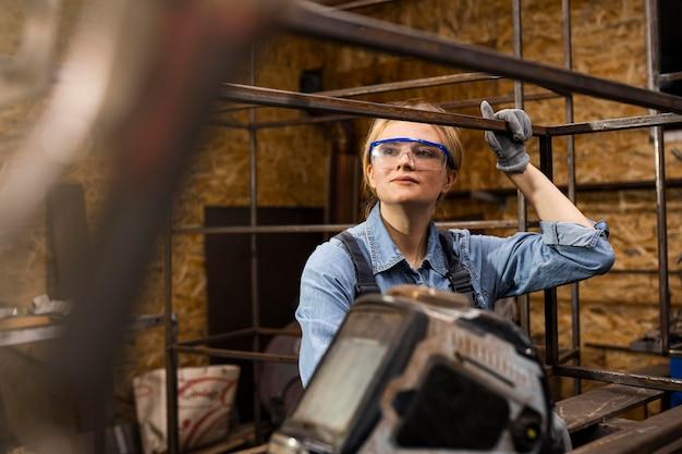 Vista frontale del saldatore femminile al lavoro