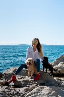 海辺でプードルと正面の女性