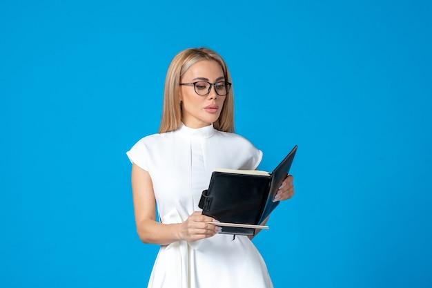 Vista frontale della lavoratrice in bellissimo abito bianco con blocco note sulla parete blu