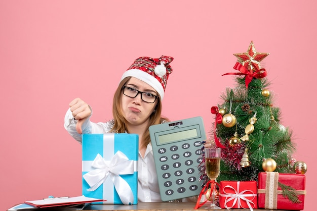 Front view of female worker holding calculator around presents on pink