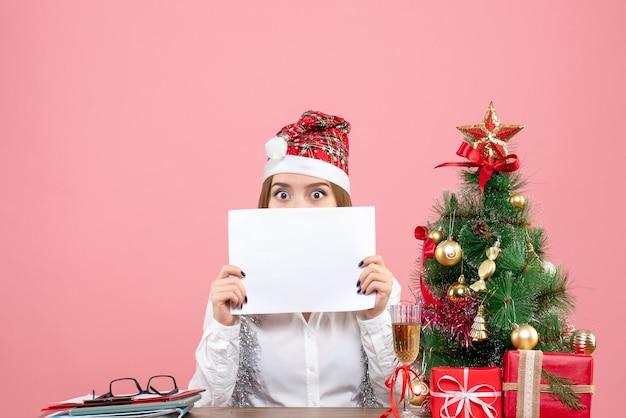 Vista frontale della lavoratrice in possesso di documenti in rosa