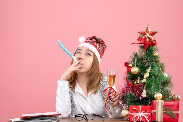 Vista frontale della lavoratrice che tiene un bicchiere di champagne in rosa