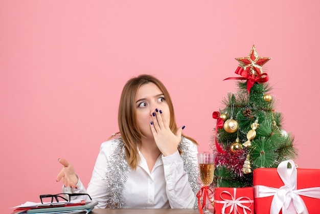 Front view of female worker sitting around christmas presents on pink