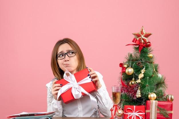 Vista frontale della lavoratrice che si siede intorno ai regali di natale e all'albero sul rosa