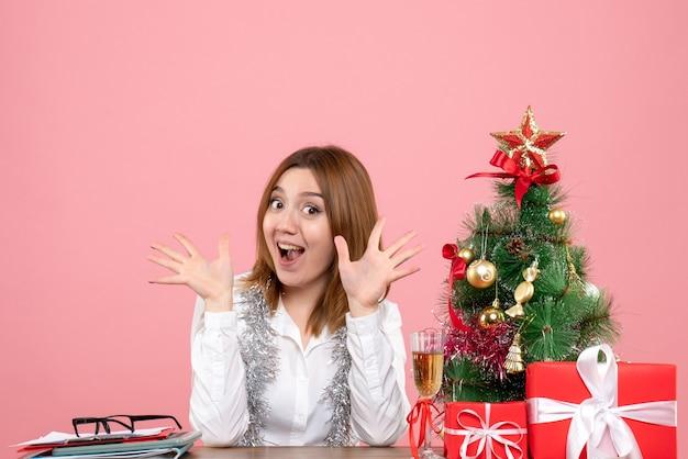 Vista frontale della lavoratrice seduta dietro il suo tavolo con la faccia eccitata su rosa chiaro