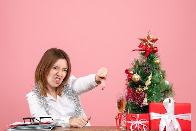Vista frontale della lavoratrice seduta dietro il suo tavolo con regali in rosa