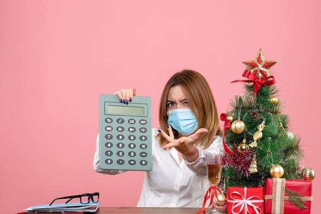 Vista frontale della lavoratrice in maschera sterile tenendo il calcolatore sul rosa