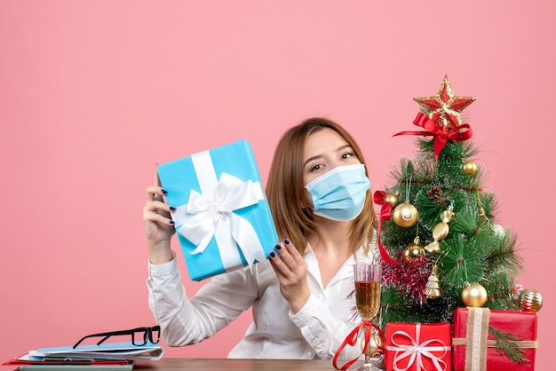 Front view of female worker in sterile mask with presents on pink