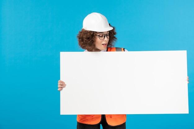 Vista frontale della lavoratrice in uniforme sulla parete blu