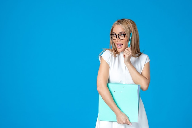 Vista frontale della lavoratrice in abito bianco che tiene cartella blu sulla parete blu