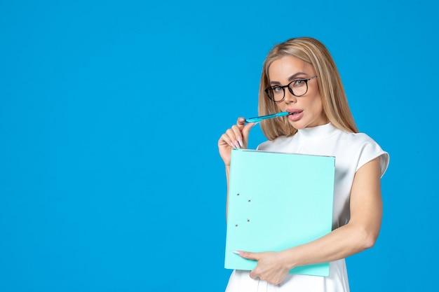 Vista frontale della lavoratrice in abito bianco che tiene la cartella sulla parete blu