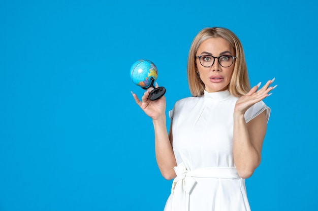 Front view of female worker in white dress holding little earth globe on blue wall