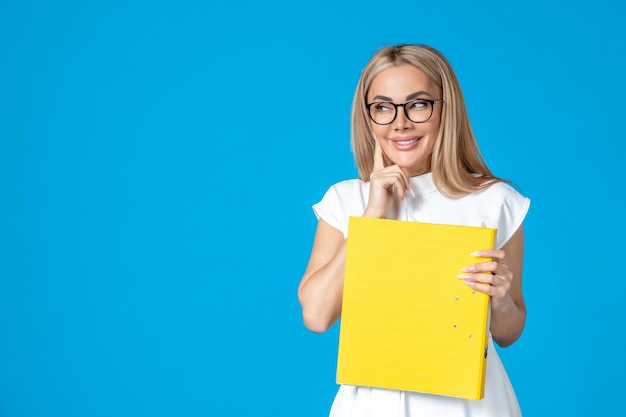 Front view of female worker in white dress holding yellow folder and smiling on blue wall