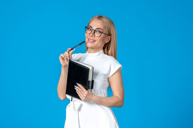 Front view of female worker in white dress posing with notepad on blue wall