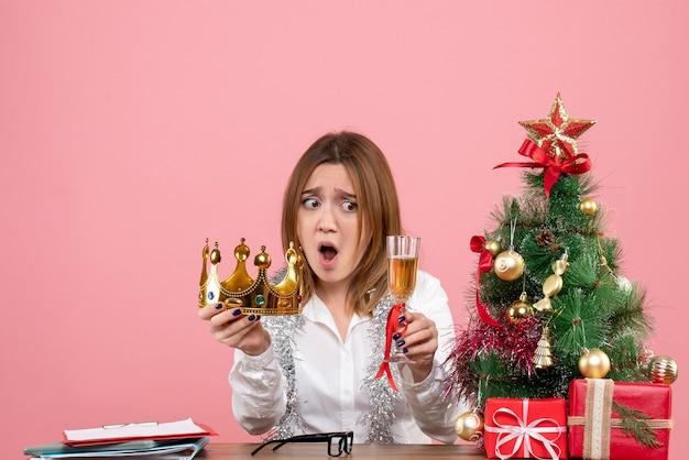 Vista frontale della lavoratrice con corona e bicchiere di champagne in rosa.