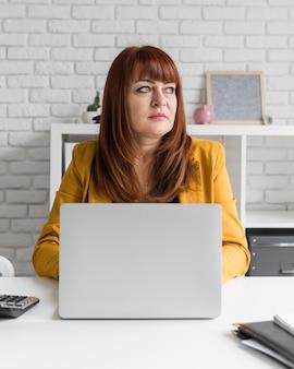 Femmina di vista frontale che lavora al computer portatile