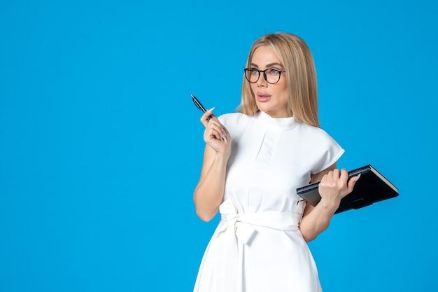 파란색 작업 기관 문서에 메모장으로 포즈를 취하는 흰색 드레스를 입은 전면 보기 여성