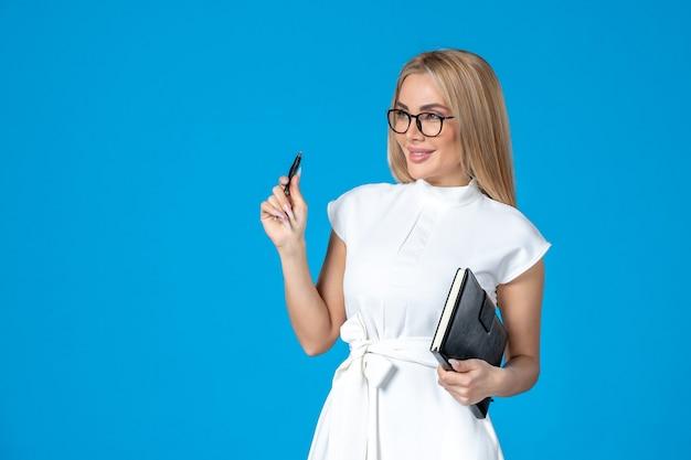 파란색 작업 기관에 메모장으로 포즈를 취하는 흰색 드레스를 입은 전면 보기 여성