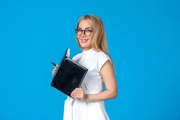 파란색 작업에 메모장으로 포즈를 취하는 흰 드레스를 입은 전면 보기 여성