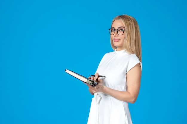 Femmina vista frontale in abito bianco in posa con blocco note sull'autorità di lavoro blu