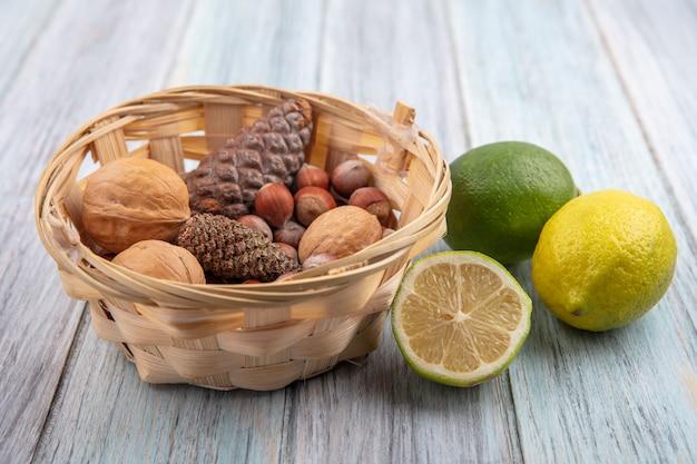 Вид спереди еловые шишки с грецкими орехами и лесными орехами в корзине и лаймами на сером фоне