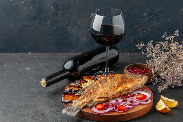 Вид спереди жареная рыба, жареные баклажаны, нарезанный лук на деревянной доске, бутылка вина и бокал на темном фоне
