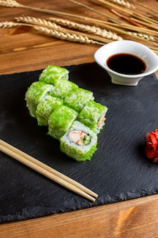 A front view fish rolls green colored filled with sliced vegetables rice along with black sauce meal fish japan