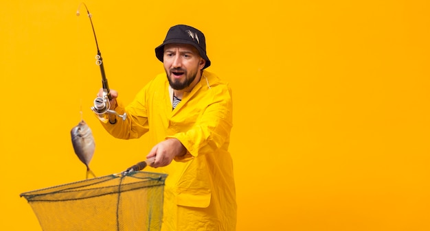 Front view of fisherman holding fishing rod and net with copy space