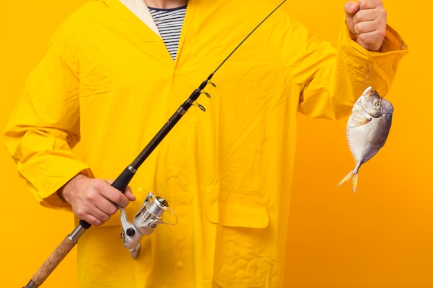 Front view of fisherman holding fishing rod with catch