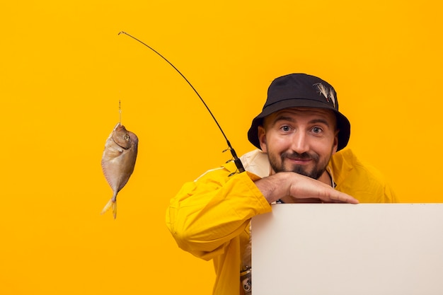 Front view of fisherman posing while holding fishing rod with catch