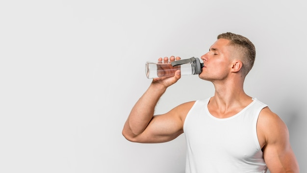 Front view of fit man drinking from water bottle with copy space