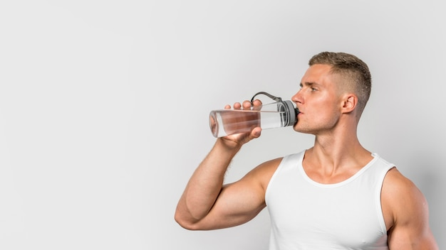 Front view of fit man drinking from water bottle