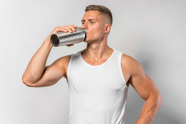 Front view of fit man drinking water