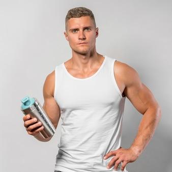 Vista frontale dell'uomo in forma in posa tenendo la bottiglia d'acqua