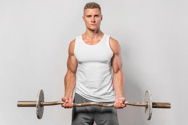 Vista frontale dell'uomo in forma in posa tenendo i pesi
