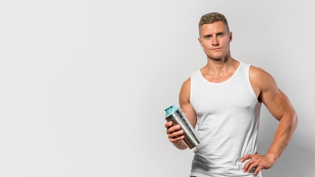 Front view of fit man posing while wearing  tank top and holding water bottle