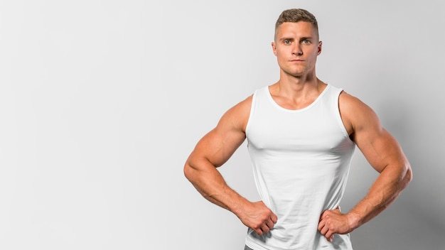 Front view of fit man posing while wearing tank top with copy space