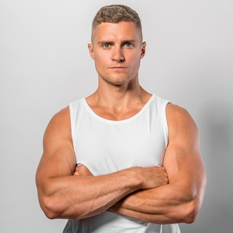 Front view of fit man posing while wearing tank top with crossed arms