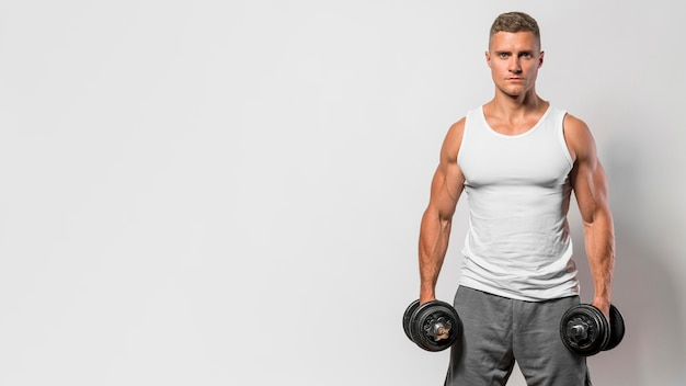 Front view of fit man with tank top and copy space