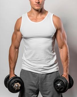 Vista frontale dell'uomo in forma con canotta e pesi