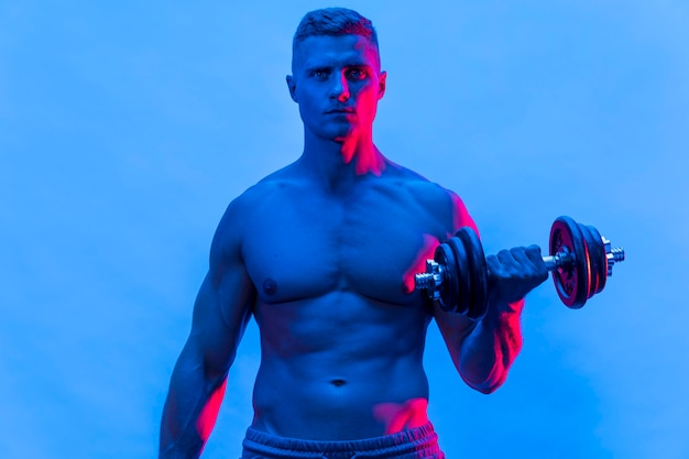 Front view of fit shirtless man exercising with weights